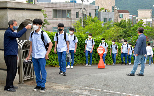 Students wearing face masks to help protect against the spread of the new coronavirus stand in a line to have their body temperatures checked before entering their classrooms at a high school in Ulsan, South Korea, Wednesday, Jun 3, 2020. (Bae Byung-soo/Newsis via AP)
