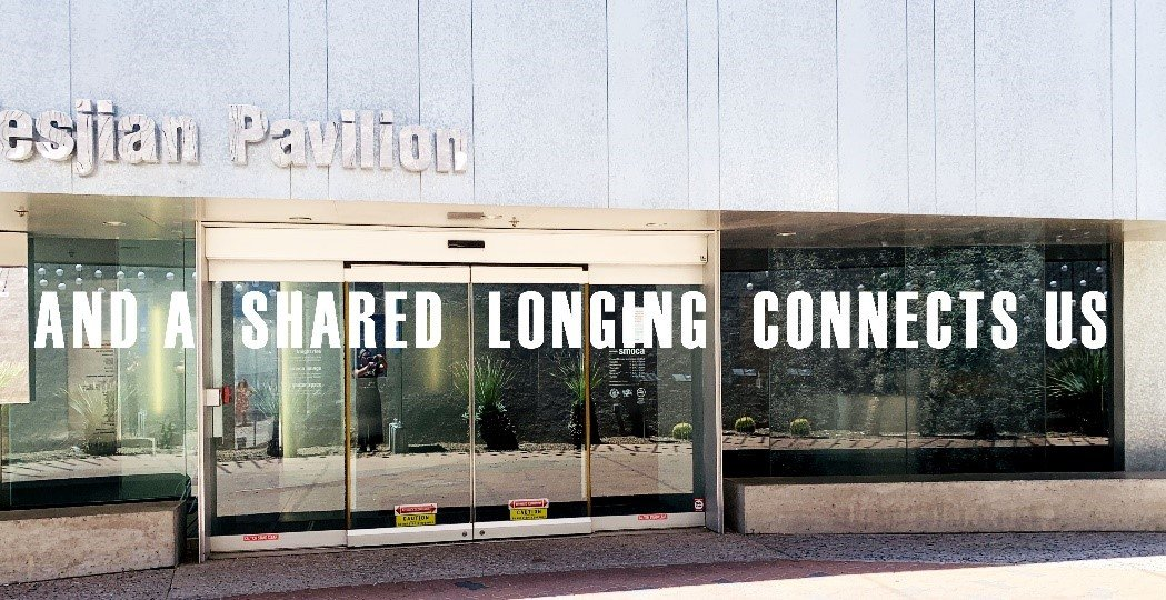 "Installed text work on the main entry of SMoCA exterior displaying, ""AND A SHARED LONGING CONNECTS US."""