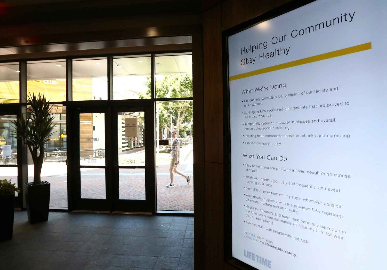 Posted signs remind clients of the social distancing and hygiene rules at Life Time health club as it remains open even as Arizona Gov. Doug Ducey has issued an executive order for all gyms to close due to the surge in coronavirus cases in Arizona Thursday, July 2, 2020, in Phoenix.