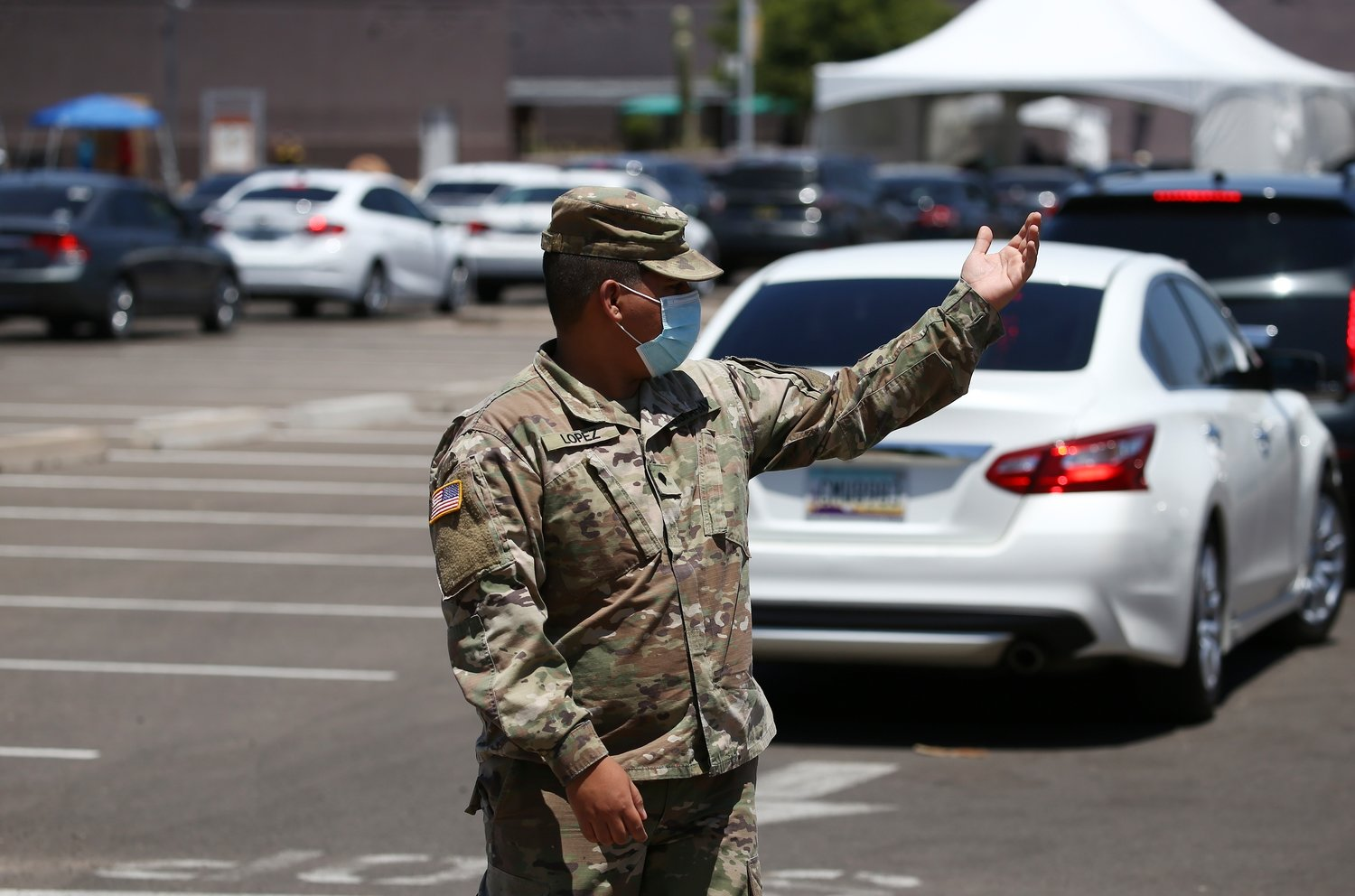 A member of the National Guard directs traffic as people wait in line to get tested at a drive thru coronavirus testing site at South Mountain Community College, Thursday, July 9, 2020, in Phoenix.