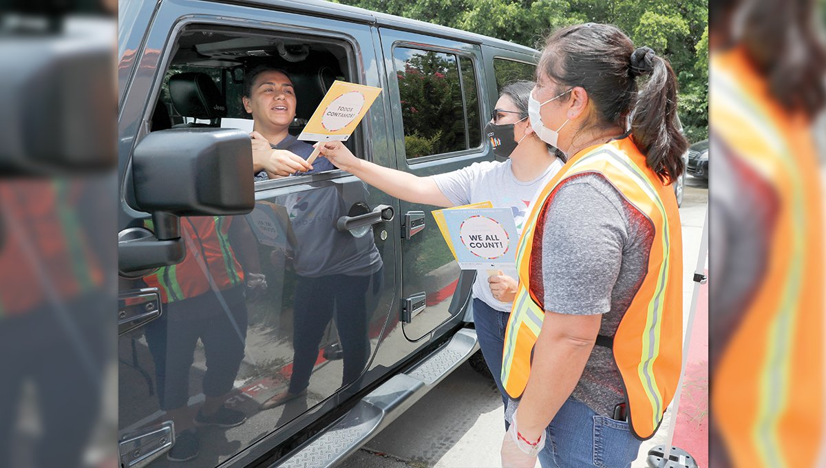 Violeta Alvarado, in vehicle, takes a fan from Leticia Tudon, center, of the nonprofit group The Concilio as Ms. Tudon and Patricia Vega, front, provide information to Ms. Alvarado about the 2020 U.S. Census at an outreach event in Dallas last month. [The Associated Press]