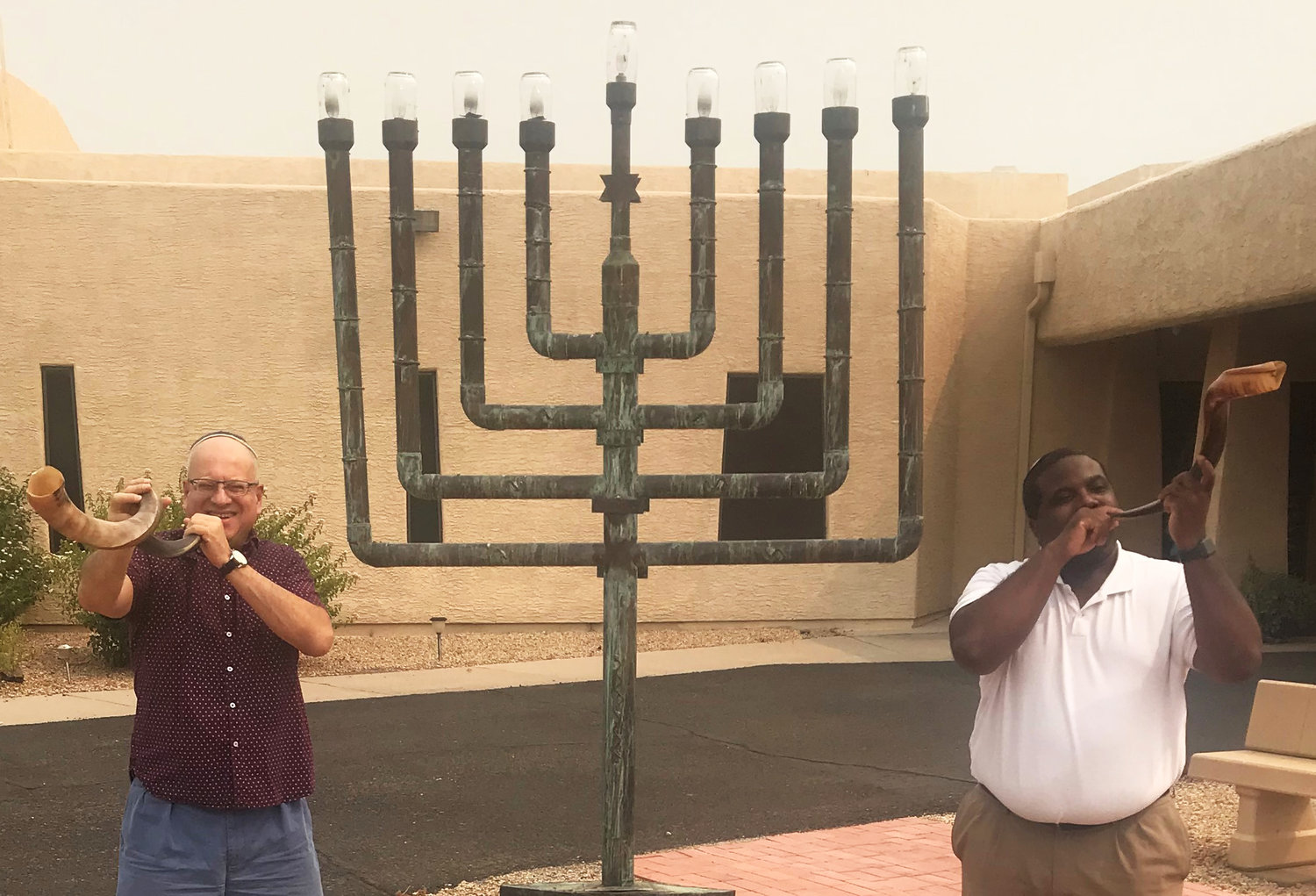 Rabbi Kaplan, left, and Andre Ivory practice blowing the shofar (ram's horn) while social distancing outside at Temple Beth Shalom in Sun City.