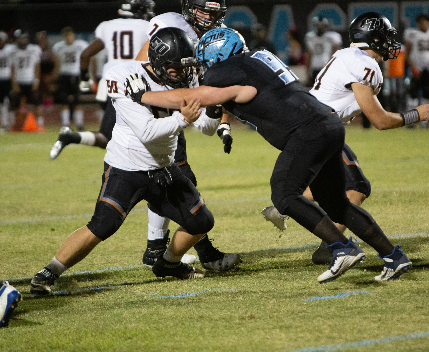 Cactus junior defensive tackle Ethan Price, right, locks up with Desert Edge senior center Braxton Matteson during an Oct. 11 game at Cactus High School in Glendale. Price is in the midst of a COVID-19 altered recruiting process.