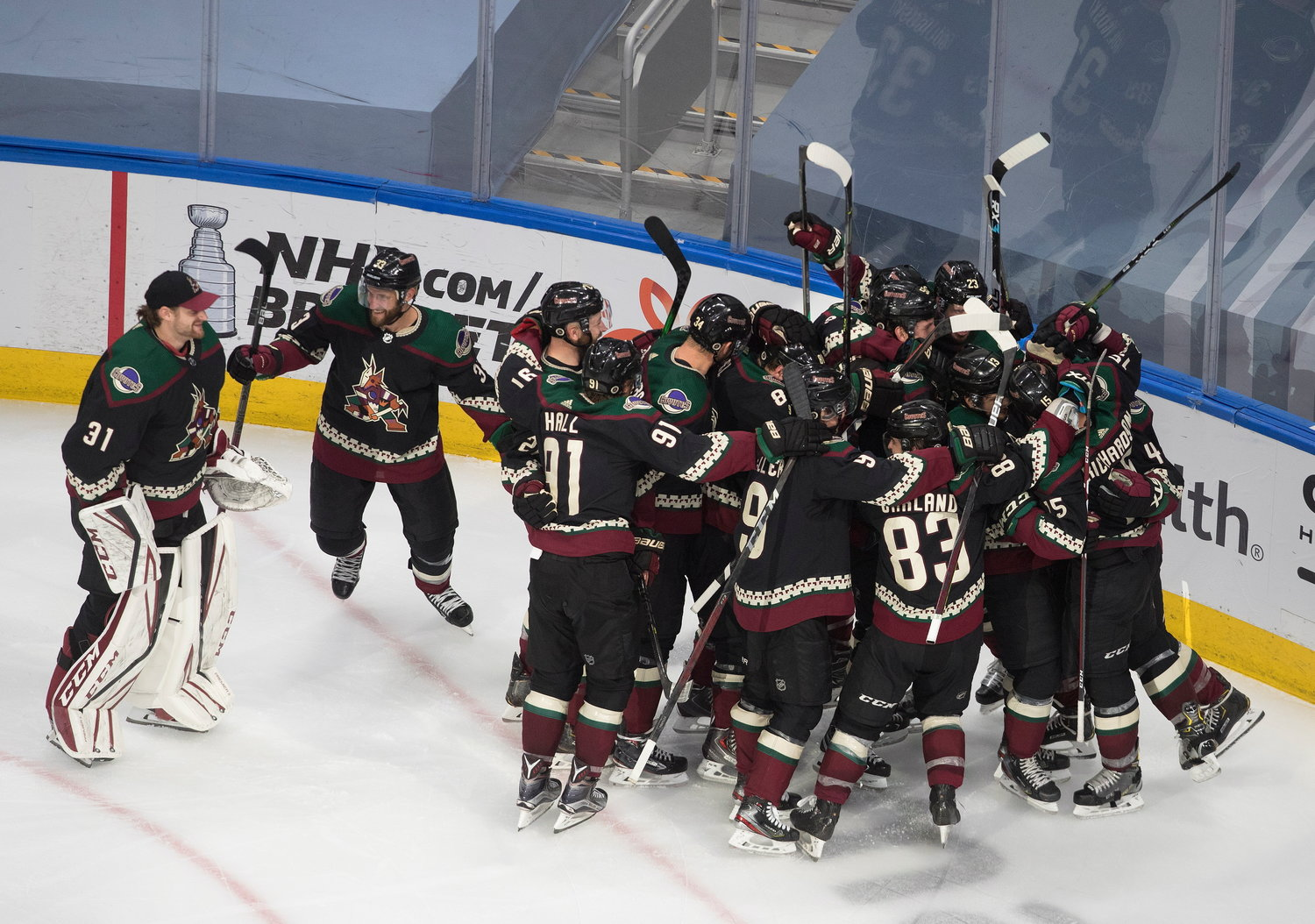 Arizona Coyotes celebrate their win over the Nashville Predators following overtime of an NHL hockey playoff game Friday, Aug. 7, 2020, in Edmonton, Alberta. (Jason Franson/Canadian Press via AP)