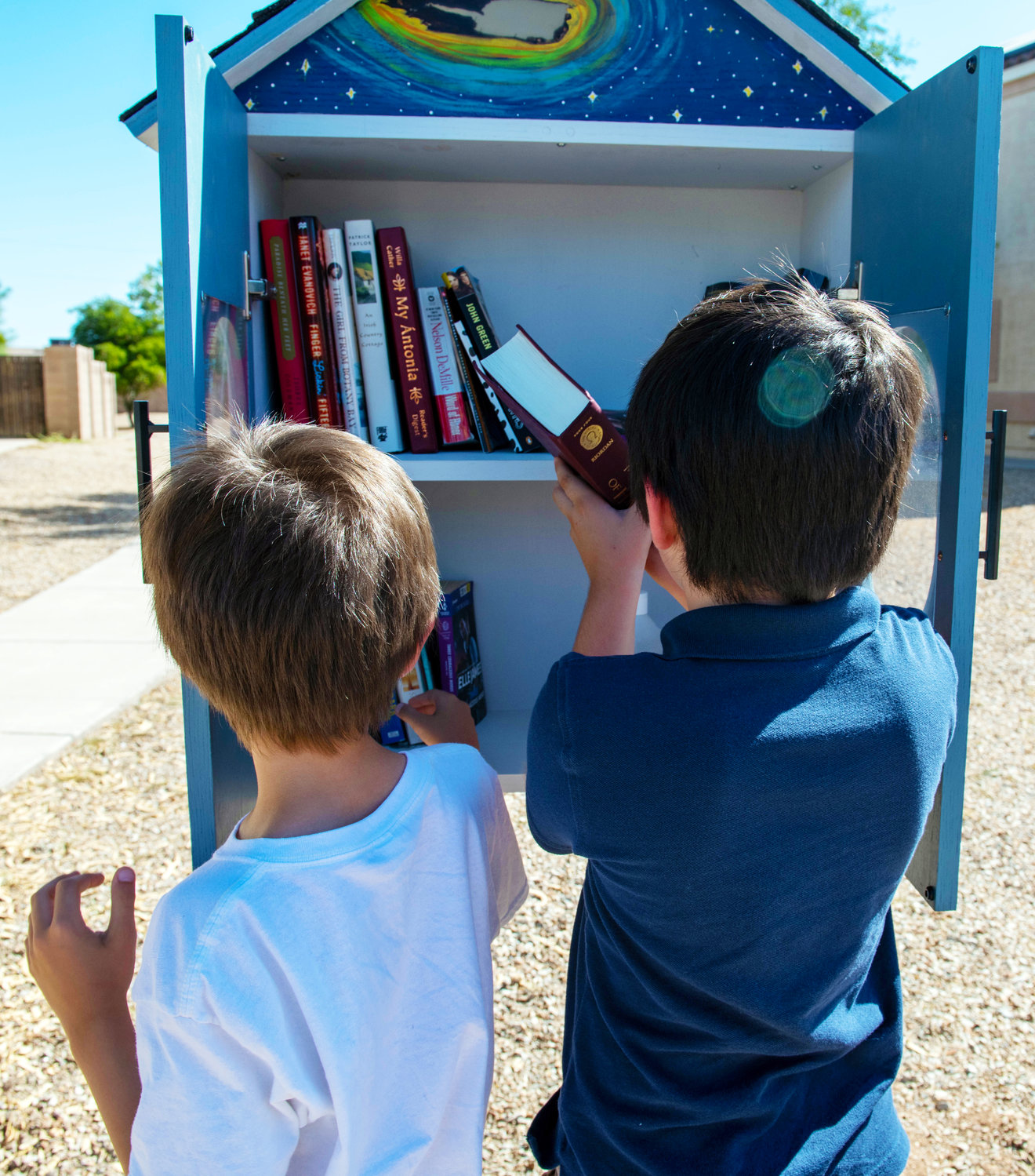 Two brothers return books to the Ocotillo Manor loaner library at Luke Air Force Base, July 28. The structure provides free books for families to take and leave a new one in its place.