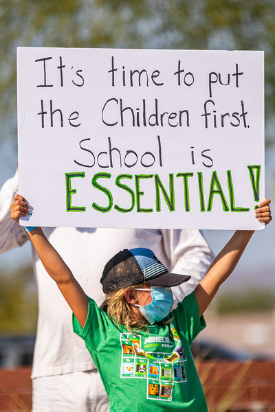 A Scottsdale Unified School District child displays a sign at a recent rally to open district schools that are phasing in campus returns for students.