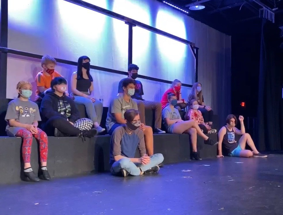 The cast of Les Miserables intently listens for notes at the end of a long day of rehearsal.