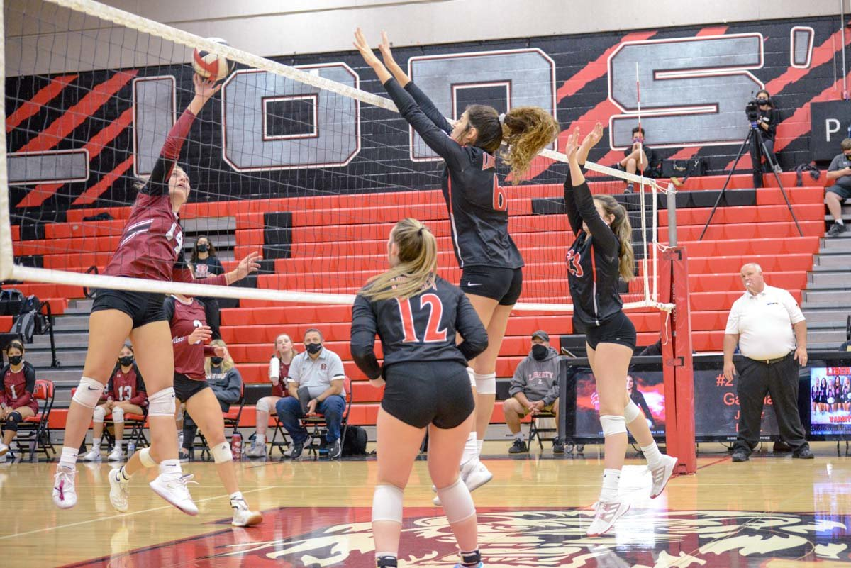 Liberty senior middle blocker Maranda Schneberger (#6) leaps to try to block an attack by Mesa Desert Ridge junior Ella Kreins. Freshman right side Aniston Smith (#23) jumps in to try and help during a Nov. 10 6A play-in game at Liberty.