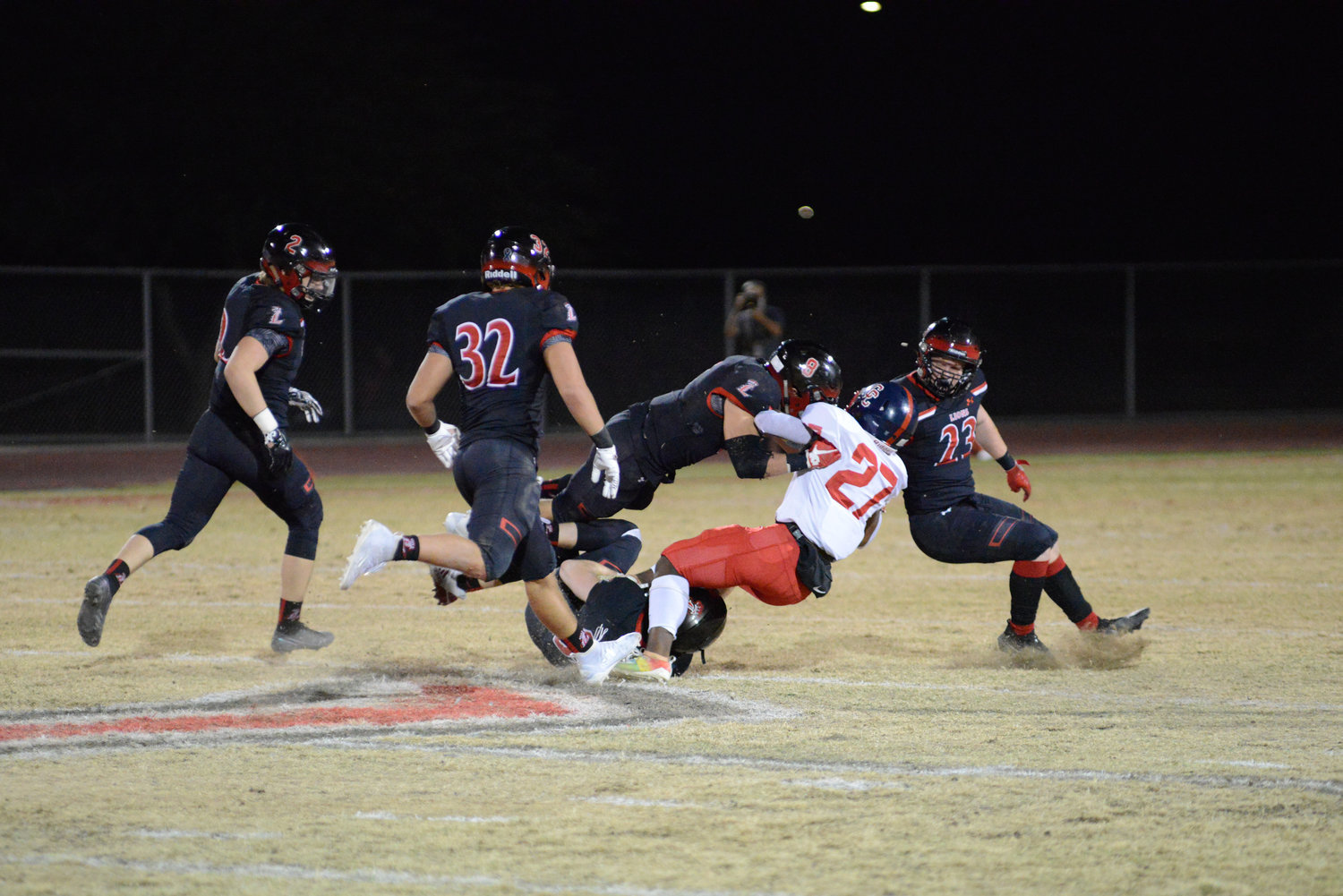 The Liberty defense, led by junior strong safety Jax Stam (leaping No. 8) and senior free safety Shane Pitts (No. 23) surrounds Centennial sophomore running back Kavaughn Clark during their regular season showdown Nov. 20 at Liberty High School in Peoria. Stam and Clark are first-team All West Valley Preps players as underclassmen. Pitts is the overall player of the year for his play on the Lions defense and as its kicker.