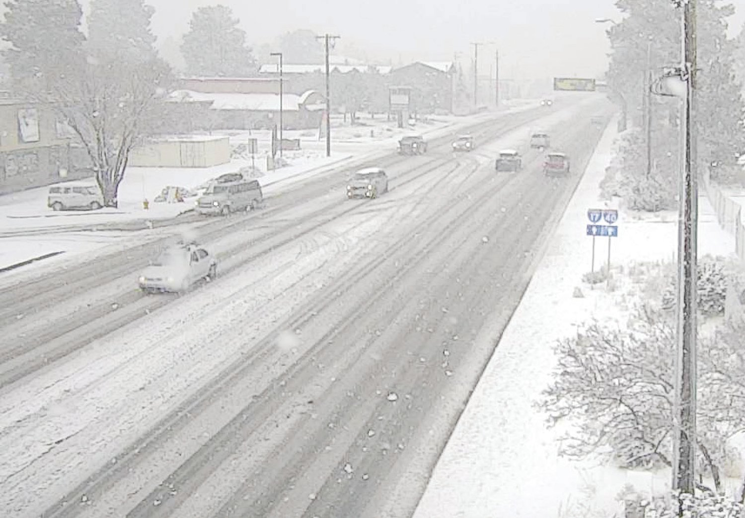 Snow falls on a roadway near Flagstaff in this webcam image. [Courtesy of ADOT]