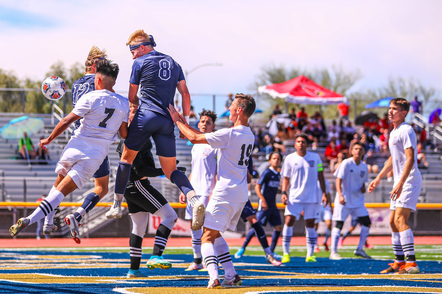 Casteel senior defender Dillon Crowder emerges above the crowd including Ironwood senior defender Jesus Medina (#7) and Colts teammate Tristain  Hughes to head in a goal during the first half of the 5A boys soccer final March 20 at Desert Vista High School in Phoenix.