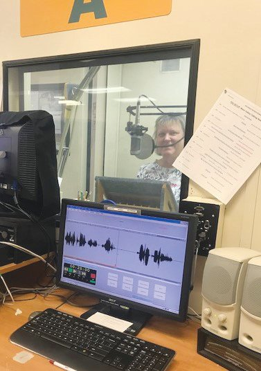 New volunteer Tina Britton is in the sound booth of studio A, where the financial news is recorded for the West Valley Talking News. [Submitted photo]