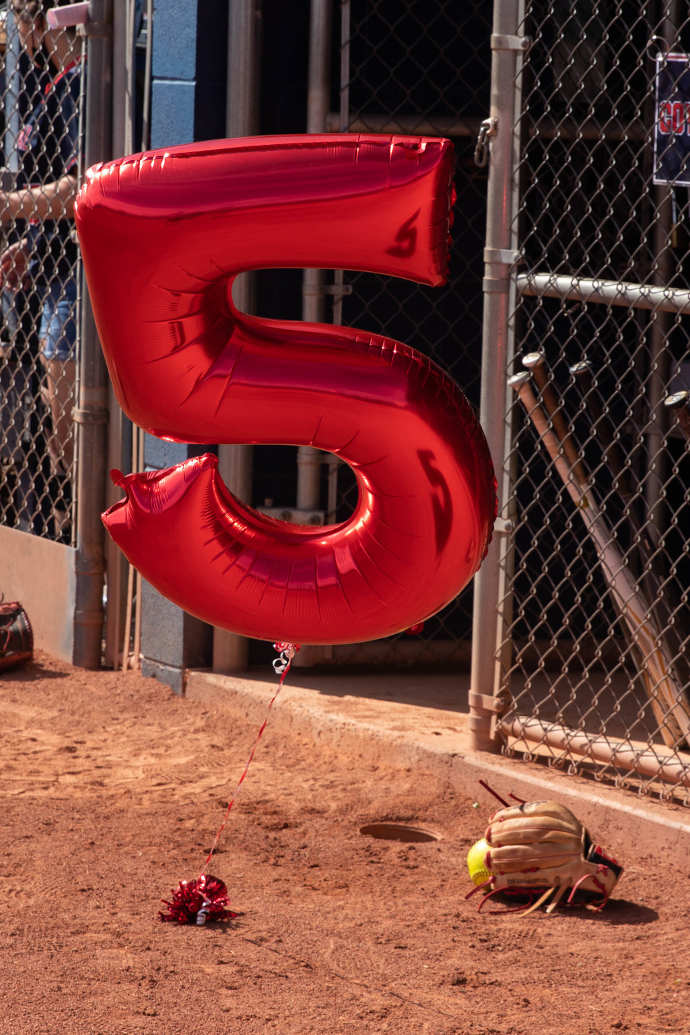 A balloon honoring the life of Ashlie Mumma (Rosenberg) with her number floats outside the Centennial softball dugout April 13.