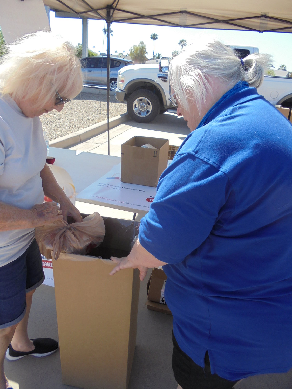 Sun City Posse members June Bryant, left, and Cheryl Fallon collect bottles of unused prescription drugs that will be sealed and then burned. It was all part of the Posse's Take-Back-Drug Initiative in cooperation with the Maricopa County Sheriff's Office.